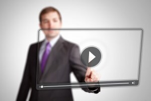 Smart businessman pressing play on a transparent futuristic looking hologram video player.